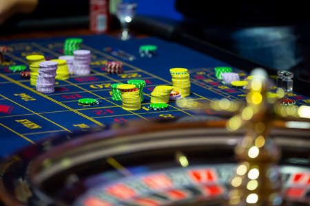 Roulette table with human hands putting down chips in casino. Roulette wheel in the foreground. Gamble game. Unrecognizable people. Stock Photo
