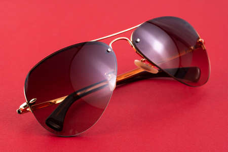 Studio shot of brown aviator sunglasses on red background. Banque d'images
