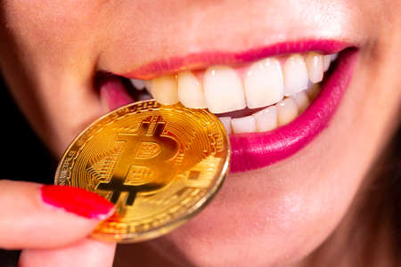 Virtual cryptocurrency money Bitcoin golden coin in the mouth of a woman with red nail polish. Beautiful female model smiling. The future of money. Coin bitten. Stock Photo