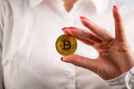Virtual cryptocurrency money Bitcoin golden coin in the left hand of a woman with red nail polish. The future of money.