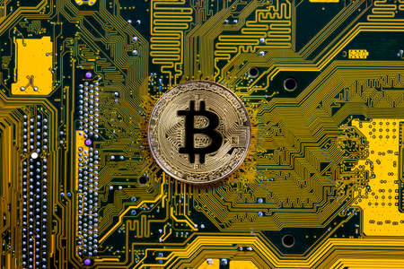 Virtual cryptocurrency money Bitcoin golden coin on a computer printed circuit board PCB. The future of money. Computational equipment. Yellow and green mother board. Shot directly from above.