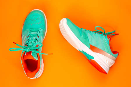Red, cyan, white pair of new tennis shoes in studio shot over orange background. Directly from above. 免版税图像