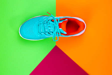 Red, cyan, white new tennis shoe in studio shot over green, orange, purple background. Directly from above.