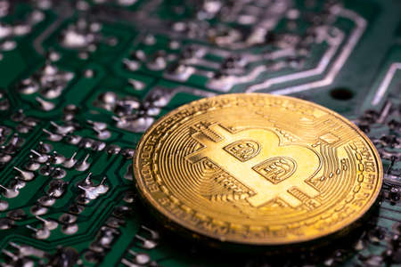 Virtual cryptocurrency money Bitcoin golden coin on a green computer printed circuit board PCB. The future of money. Computational equipment. Dark image. Reklamní fotografie