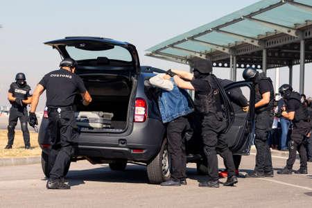 I funzionari della dogana e della protezione delle frontiere e le forze speciali dell'amministrazione antidroga partecipano a un corso di formazione in aeroporto per la ricerca e il sequestro di droghe illegali. Persone irriconoscibili in nero.