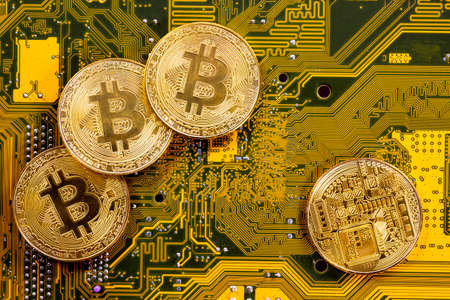 Virtual cryptocurrency money Bitcoin golden coins on a computer printed circuit board PCB. The future of money. Computational equipment. Yellow and green mother board. Shot directly from above. Reklamní fotografie