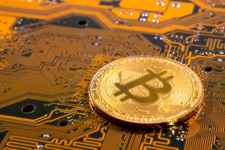 Virtual cryptocurrency money Bitcoin golden coin on a computer printed circuit board PCB. The future of money. Computational equipment. Yellow and green mother board. Reklamní fotografie