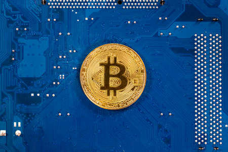 Virtual cryptocurrency money Bitcoin golden coin on a computer printed circuit board PCB. The future of money. Computational equipment. Blue mother board. Shot directly from above.