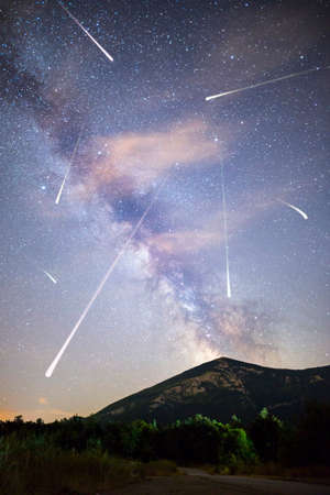 A view of a Meteor Shower and the Milky Way with a mountain top in the foreground. Night sky nature summer landscape. Perseid Meteor Shower observation. Rtanj mountain in Serbia. Vertical image.
