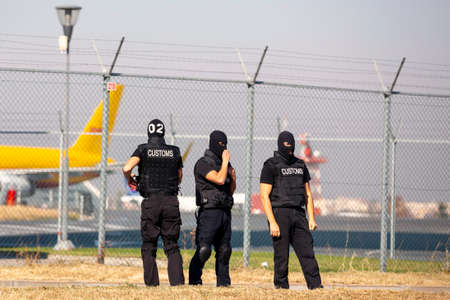 Three customs and border protection officers and Drug enforcement administration special forces participate in a training at the airport for searching and seizing of illegal drugs. Unrecognizable peop