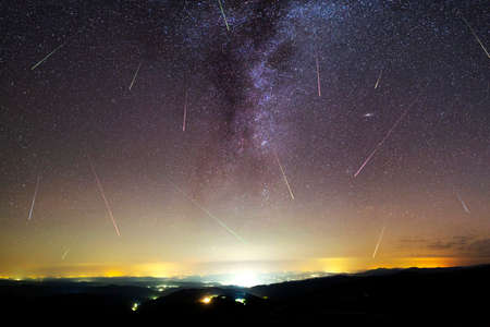 A view of a Meteor Shower and the Milky Way with an illuminated city silhouette in the foreground. Night sky nature summer landscape. Perseid Meteor Shower observation. Colorful shooting stars. Stok Fotoğraf