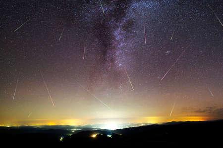 Una vista de una lluvia de meteoritos y la Vía Láctea con una silueta de ciudad iluminada en primer plano. Paisaje de verano de naturaleza de cielo nocturno. Observación de la lluvia de meteoritos de las Perseidas. Estrellas fugaces de colores. Foto de archivo
