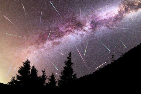 A view of a Meteor Shower and the purple Milky Way with pine trees forest silhouette in the foreground. Perseid Meteor Shower observation. Night sky nature summer landscape. Colorful shooting stars.