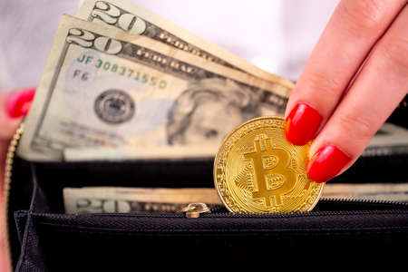 Virtual cryptocurrency money Bitcoin golden coins in the left hand of a woman with red nail polish and a purse. The future of money. US dollars. Zdjęcie Seryjne