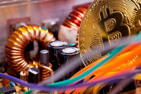 Virtual cryptocurrency money Bitcoin golden coin on a computer printed circuit board PCB surrounded by different colorful cables. The future of money. Computational equipment. Zdjęcie Seryjne