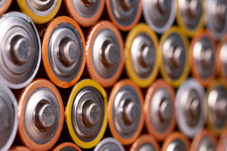 Multiple used AA alkaline batteries are seen arranged in a pile. Closeup side view from the plus side of the battery. Stock fotó