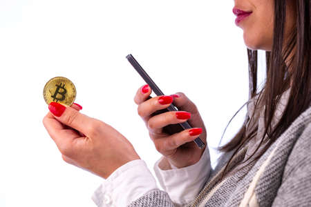 Virtual cryptocurrency money Bitcoin golden coin in the left hand of a woman with red nail polish. Beautiful female model smiling. The future of money. Isolated on a white background. Banco de Imagens