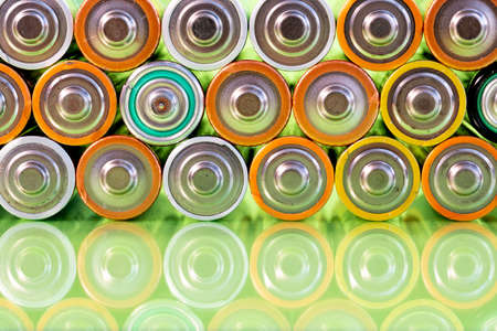 Multiple used AA alkaline batteries are seen arranged in a pile on a reflective green surface. Closeup front view from the plus side of the battery.