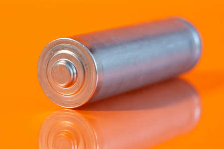 Single used AA alkaline battery is seen on a reflective orange surface. Closeup side view from the plus side of the battery.