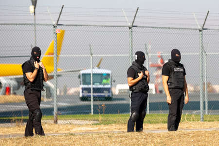 Three customs and border protection officers and Drug enforcement administration special forces participate in a training at the airport for searching and seizing of illegal drugs. Unrecognizable people in black.