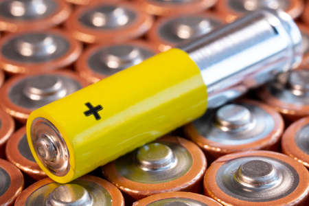Multiple used AA alkaline batteries and a single AAA battery are seen arranged in a pile. Closeup side view from the plus side of the battery. Single yellow AAA battery.