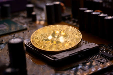 Virtual cryptocurrency money Bitcoin golden coin on a computer printed circuit board PCB. The future of money. Computational equipment.