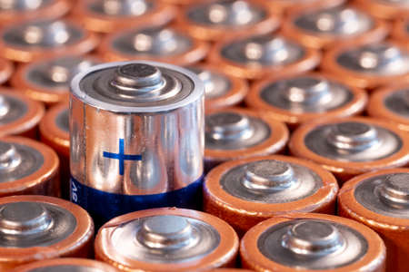 Multiple used AA alkaline batteries are seen arranged in a pile. Closeup side view from the plus side of the battery. Blue plus side of a battery.