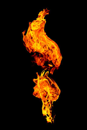 Burning flame isolated on a black background. Fire in red, orange and yellow. Vertical orientation image. Фото со стока