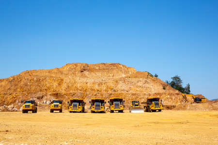 Gold mine dump trucks and excavator are seen in an opencast quarry. Heavy machinery. Blue sky.