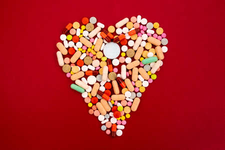 Different colorful pills and capsules in full heart shape on a red background. Global pharmaceutical industry for billions dollars per year. Pharmaceutical drugs for use as medications. Studio shot.