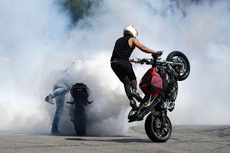 Two motorbikes burn wheels on a race track. White smoke.