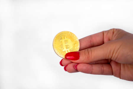 Virtual cryptocurrency money Bitcoin golden coin in the right hand of a woman with red nail polish. The future of money. Isolated on a white background. Stock Photo