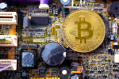 Virtual cryptocurrency money Bitcoin golden coin on a computer printed circuit board PCB. The future of money. Computational equipment. Shot directly from above. Lithium battery. Reklamní fotografie