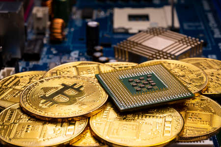 Virtual cryptocurrency money Bitcoin golden coins and CPU on a computer printed circuit board PCB. The future of money. Computational equipment.