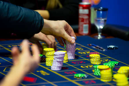 Roulette table with human hands putting down chips in casino. Roulette wheel in the foreground. Gamble game. Unrecognizable people. 스톡 콘텐츠