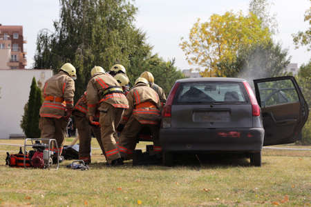 Firefighters participate in a training where they extinguish fire from a car crashed into another vehicle. Smoke from a blue car after an explosion.