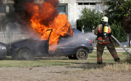Firefighters participate in a training where they extinguish fire from a car crashed into another vehicle. Fire blaze from a blue car after an explosion.