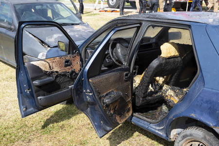 A blue car is seen after it has crashed into another vehicle and catched in fire.
