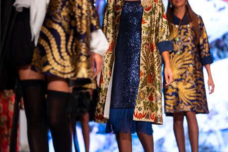 Weibliche Models laufen während einer Fashion Show in schönen Designerkleidern über den Laufsteg. Mode-Laufsteg-Event mit neuer Kleiderkollektion. Unerkennbare Menschen.