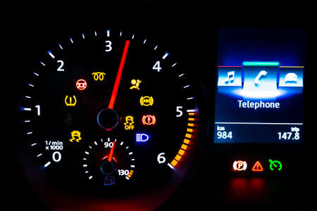 Modern light car mileage (dashboard, milage) isolated on a black background. New display of a modern car. Telephone.
