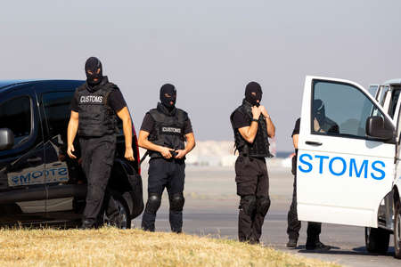 Customs and border protection officers and Drug enforcement administration special forces participate in a training at the airport for searching and seizing of illegal drugs. Unrecognizable people in black. Stock Photo