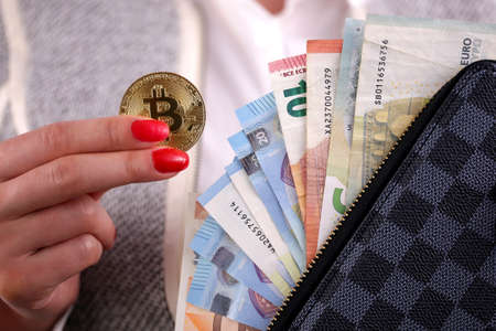 Virtual cryptocurrency money Bitcoin golden coins in the left hand of a woman with red nail polish and a purse. The future of money. Euro banknotes. Banco de Imagens