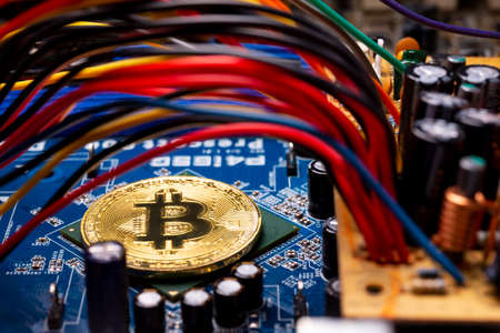 Virtual cryptocurrency money Bitcoin golden coin on a computer printed circuit board PCB surrounded by different colorful cables. The future of money. Computational equipment. Reklamní fotografie