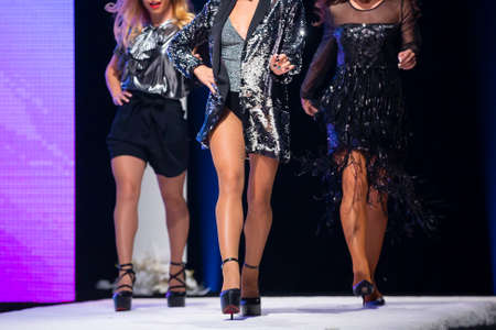 Three female models walk the runway in beautiful designer dresses during a Fashion Show. Imagens