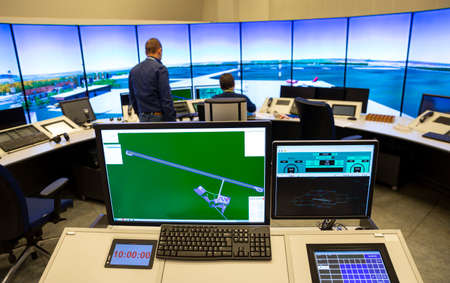 Air traffic control simulator station. Green monitor screen in the foreground. Trainer in the background.
