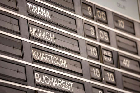 Old flight information display system. Split-flap (or just flap) display. Often used as a public transport timetable in airports or railway stations. Tirana, Munich, Khartoum, Bucharest.