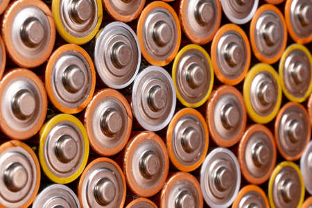Multiple used AA alkaline batteries are seen arranged in a pile. Closeup side view from the plus side of the battery. Archivio Fotografico