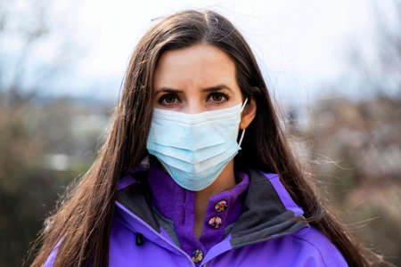 Young woman wearing a protective surgical face mask during the Coronavirus disease (COVID-19) outbreak epidemic. Close up portrait with a single use blue protection mask on the face. Looking at camera