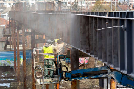 A worker in protective work wear incluing gas mask sprays overpass with anti rust primer. 免版税图像