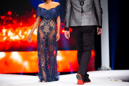 Female and male models walk the runway in beautiful designer clothes during a Fashion Show. Fashion catwalk event showing new collection of clothes. Unrecognizable people. 免版税图像